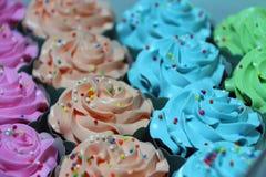 Η σειρά του πορτοκαλιού, μπλε, πράσινος και ρόδινος του κέικ φλυτζανιών με τις ζωηρόχρωμες στρογγυλευμένες χάντρες ζάχαρης στην κ Στοκ Φωτογραφία