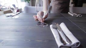 Η σερβιτόρα βάζει το γυαλί στον πίνακα απόθεμα βίντεο