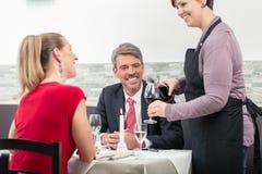 Η σερβιτόρα εξυπηρετεί το κρασί που συνδέει στοκ εικόνες