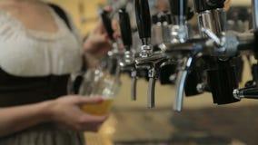 Η σερβιτόρα χύνει μια μπύρα από τη βρύση μπύρας απόθεμα βίντεο