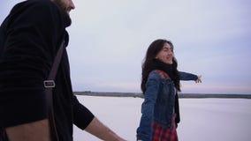 Η σε αργή κίνηση φίλη και ο φίλος που περπατούν στην παραλία ψάχνουν τη θέση για το πρόχειρο φαγητό απόθεμα βίντεο