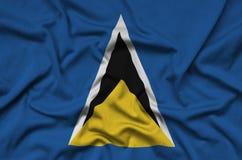 Η σημαία Αγιών Λουκία απεικονίζεται σε ένα ύφασμα αθλητικών υφασμάτων με πολλές πτυχές Έμβλημα αθλητικών ομάδων στοκ φωτογραφία με δικαίωμα ελεύθερης χρήσης