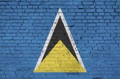Η σημαία Αγιών Λουκία είναι χρωματισμένη επάνω σε έναν παλαιό τουβλότοιχο στοκ φωτογραφίες