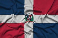 Η σημαία Δομινικανής Δημοκρατίας απεικονίζεται σε ένα ύφασμα αθλητικών υφασμάτων με πολλές πτυχές Έμβλημα αθλητικών ομάδων στοκ φωτογραφία με δικαίωμα ελεύθερης χρήσης