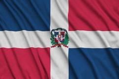 Η σημαία Δομινικανής Δημοκρατίας απεικονίζεται σε ένα ύφασμα αθλητικών υφασμάτων με πολλές πτυχές Έμβλημα αθλητικών ομάδων στοκ εικόνα με δικαίωμα ελεύθερης χρήσης