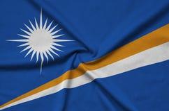 Η σημαία Νησιών Μάρσαλ απεικονίζεται σε ένα ύφασμα αθλητικών υφασμάτων με πολλές πτυχές Έμβλημα αθλητικών ομάδων στοκ εικόνα με δικαίωμα ελεύθερης χρήσης