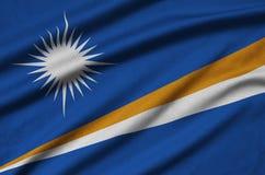 Η σημαία Νησιών Μάρσαλ απεικονίζεται σε ένα ύφασμα αθλητικών υφασμάτων με πολλές πτυχές Έμβλημα αθλητικών ομάδων στοκ φωτογραφίες με δικαίωμα ελεύθερης χρήσης