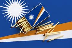 Η σημαία Νησιών Μάρσαλ παρουσιάζεται σε ένα ανοικτό σπιρτόκουτο, από το οποίο διάφορες αντιστοιχίες αφορούν και βρίσκονται μια με στοκ εικόνα με δικαίωμα ελεύθερης χρήσης