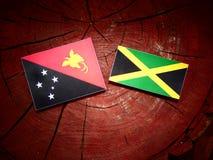 Η σημαία Παπούα Νέα Γουϊνέα με την τζαμαϊκανή σημαία σε ένα κολόβωμα δέντρων απομονώνει Στοκ Εικόνες