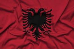 Η σημαία της Αλβανίας απεικονίζεται σε ένα ύφασμα αθλητικών υφασμάτων με πολλές πτυχές Έμβλημα αθλητικών ομάδων στοκ εικόνα με δικαίωμα ελεύθερης χρήσης