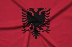 Η σημαία της Αλβανίας απεικονίζεται σε ένα ύφασμα αθλητικών υφασμάτων με πολλές πτυχές Έμβλημα αθλητικών ομάδων στοκ φωτογραφία με δικαίωμα ελεύθερης χρήσης