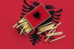 Η σημαία της Αλβανίας παρουσιάζεται σε ένα ανοικτό σπιρτόκουτο, από το οποίο διάφορες αντιστοιχίες αφορούν και βρίσκονται μια μεγ στοκ φωτογραφία με δικαίωμα ελεύθερης χρήσης