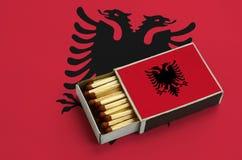 Η σημαία της Αλβανίας παρουσιάζεται σε ένα ανοικτό σπιρτόκουτο, το οποίο γεμίζουν με τις αντιστοιχίες και βρίσκεται σε μια μεγάλη στοκ εικόνα