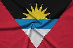 Η σημαία της Αντίγκουα και της Μπαρμπούντα απεικονίζεται σε ένα ύφασμα αθλητικών υφασμάτων με πολλές πτυχές Έμβλημα αθλητικών ομά στοκ φωτογραφία με δικαίωμα ελεύθερης χρήσης