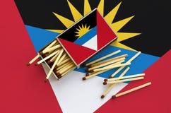 Η σημαία της Αντίγκουα και της Μπαρμπούντα παρουσιάζεται σε ένα ανοικτό σπιρτόκουτο, από το οποίο διάφορες αντιστοιχίες αφορούν κ στοκ εικόνες