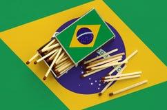 Η σημαία της Βραζιλίας παρουσιάζεται σε ένα ανοικτό σπιρτόκουτο, από το οποίο διάφορες αντιστοιχίες αφορούν και βρίσκονται μια με στοκ φωτογραφία