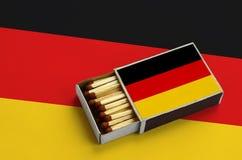 Η σημαία της Γερμανίας παρουσιάζεται σε ένα ανοικτό σπιρτόκουτο, το οποίο γεμίζουν με τις αντιστοιχίες και βρίσκεται σε μια μεγάλ στοκ εικόνες