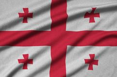 Η σημαία της Γεωργίας απεικονίζεται σε ένα ύφασμα αθλητικών υφασμάτων με πολλές πτυχές Έμβλημα αθλητικών ομάδων στοκ εικόνα με δικαίωμα ελεύθερης χρήσης