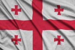 Η σημαία της Γεωργίας απεικονίζεται σε ένα ύφασμα αθλητικών υφασμάτων με πολλές πτυχές Έμβλημα αθλητικών ομάδων στοκ φωτογραφίες με δικαίωμα ελεύθερης χρήσης