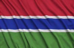 Η σημαία της Γκάμπιας απεικονίζεται σε ένα ύφασμα αθλητικών υφασμάτων με πολλές πτυχές Έμβλημα αθλητικών ομάδων στοκ φωτογραφία με δικαίωμα ελεύθερης χρήσης