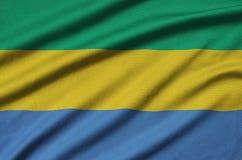 Η σημαία της Γκαμπόν απεικονίζεται σε ένα ύφασμα αθλητικών υφασμάτων με πολλές πτυχές Έμβλημα αθλητικών ομάδων στοκ φωτογραφία