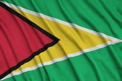 Η σημαία της Γουιάνας απεικονίζεται σε ένα ύφασμα αθλητικών υφασμάτων με πολλές πτυχές Έμβλημα αθλητικών ομάδων στοκ εικόνα