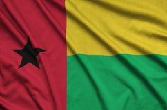 Η σημαία της Γουινέα-Μπισσάου απεικονίζεται σε ένα ύφασμα αθλητικών υφασμάτων με πολλές πτυχές Έμβλημα αθλητικών ομάδων στοκ εικόνες