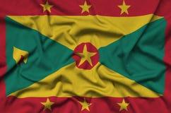 Η σημαία της Γρενάδας απεικονίζεται σε ένα ύφασμα αθλητικών υφασμάτων με πολλές πτυχές Έμβλημα αθλητικών ομάδων στοκ φωτογραφία με δικαίωμα ελεύθερης χρήσης
