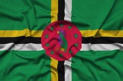 Η σημαία της Δομίνικας απεικονίζεται σε ένα ύφασμα αθλητικών υφασμάτων με πολλές πτυχές Έμβλημα αθλητικών ομάδων στοκ εικόνα με δικαίωμα ελεύθερης χρήσης