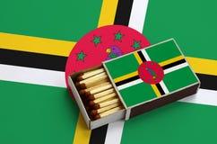 Η σημαία της Δομίνικας παρουσιάζεται σε ένα ανοικτό σπιρτόκουτο, το οποίο γεμίζουν με τις αντιστοιχίες και βρίσκεται σε μια μεγάλ στοκ φωτογραφίες με δικαίωμα ελεύθερης χρήσης