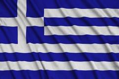Η σημαία της Ελλάδας απεικονίζεται σε ένα ύφασμα αθλητικών υφασμάτων με πολλές πτυχές Έμβλημα αθλητικών ομάδων στοκ φωτογραφία με δικαίωμα ελεύθερης χρήσης