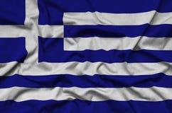 Η σημαία της Ελλάδας απεικονίζεται σε ένα ύφασμα αθλητικών υφασμάτων με πολλές πτυχές Έμβλημα αθλητικών ομάδων στοκ εικόνα