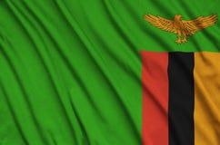 Η σημαία της Ζάμπια απεικονίζεται σε ένα ύφασμα αθλητικών υφασμάτων με πολλές πτυχές Έμβλημα αθλητικών ομάδων στοκ φωτογραφίες