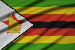 Η σημαία της Ζιμπάμπουε απεικονίζεται σε ένα ύφασμα αθλητικών υφασμάτων με πολλές πτυχές Έμβλημα αθλητικών ομάδων στοκ φωτογραφία με δικαίωμα ελεύθερης χρήσης
