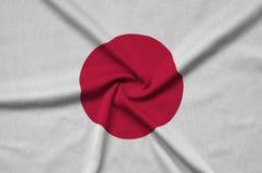 Η σημαία της Ιαπωνίας απεικονίζεται σε ένα ύφασμα αθλητικών υφασμάτων με πολλές πτυχές Έμβλημα αθλητικών ομάδων στοκ φωτογραφία με δικαίωμα ελεύθερης χρήσης