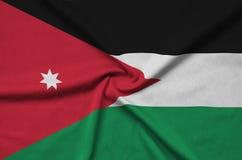 Η σημαία της Ιορδανίας απεικονίζεται σε ένα ύφασμα αθλητικών υφασμάτων με πολλές πτυχές Έμβλημα αθλητικών ομάδων στοκ φωτογραφίες με δικαίωμα ελεύθερης χρήσης