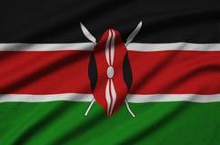 Η σημαία της Κένυας απεικονίζεται σε ένα ύφασμα αθλητικών υφασμάτων με πολλές πτυχές Έμβλημα αθλητικών ομάδων στοκ εικόνες με δικαίωμα ελεύθερης χρήσης