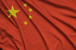 Η σημαία της Κίνας απεικονίζεται σε ένα ύφασμα αθλητικών υφασμάτων με πολλές πτυχές Έμβλημα αθλητικών ομάδων στοκ φωτογραφία