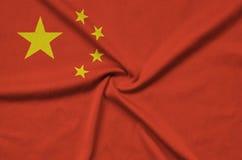 Η σημαία της Κίνας απεικονίζεται σε ένα ύφασμα αθλητικών υφασμάτων με πολλές πτυχές Έμβλημα αθλητικών ομάδων στοκ φωτογραφία με δικαίωμα ελεύθερης χρήσης