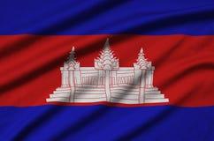 Η σημαία της Καμπότζης απεικονίζεται σε ένα ύφασμα αθλητικών υφασμάτων με πολλές πτυχές Έμβλημα αθλητικών ομάδων στοκ εικόνα με δικαίωμα ελεύθερης χρήσης
