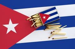 Η σημαία της Κούβας παρουσιάζεται σε ένα ανοικτό σπιρτόκουτο, από το οποίο διάφορες αντιστοιχίες αφορούν και βρίσκονται μια μεγάλ στοκ εικόνα