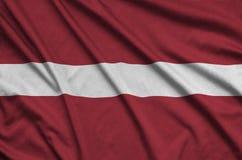 Η σημαία της Λετονίας απεικονίζεται σε ένα ύφασμα αθλητικών υφασμάτων με πολλές πτυχές Έμβλημα αθλητικών ομάδων στοκ εικόνες με δικαίωμα ελεύθερης χρήσης