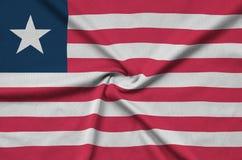 Η σημαία της Λιβερίας απεικονίζεται σε ένα ύφασμα αθλητικών υφασμάτων με πολλές πτυχές Έμβλημα αθλητικών ομάδων στοκ φωτογραφία με δικαίωμα ελεύθερης χρήσης