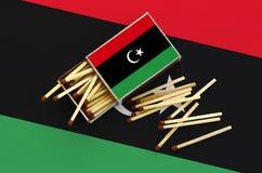 Η σημαία της Λιβύης παρουσιάζεται σε ένα ανοικτό σπιρτόκουτο, από το οποίο διάφορες αντιστοιχίες αφορούν και βρίσκονται μια μεγάλ στοκ φωτογραφία