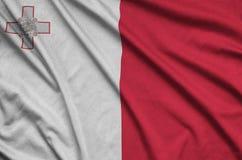 Η σημαία της Μάλτας απεικονίζεται σε ένα ύφασμα αθλητικών υφασμάτων με πολλές πτυχές Έμβλημα αθλητικών ομάδων στοκ εικόνα με δικαίωμα ελεύθερης χρήσης