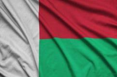 Η σημαία της Μαδαγασκάρης απεικονίζεται σε ένα ύφασμα αθλητικών υφασμάτων με πολλές πτυχές Έμβλημα αθλητικών ομάδων στοκ φωτογραφίες