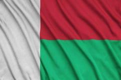 Η σημαία της Μαδαγασκάρης απεικονίζεται σε ένα ύφασμα αθλητικών υφασμάτων με πολλές πτυχές Έμβλημα αθλητικών ομάδων στοκ φωτογραφία με δικαίωμα ελεύθερης χρήσης