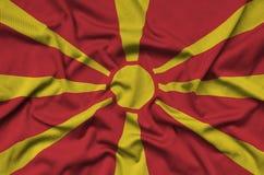 Η σημαία της Μακεδονίας απεικονίζεται σε ένα ύφασμα αθλητικών υφασμάτων με πολλές πτυχές Έμβλημα αθλητικών ομάδων στοκ εικόνες με δικαίωμα ελεύθερης χρήσης