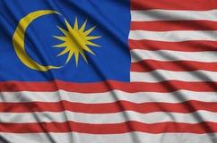 Η σημαία της Μαλαισίας απεικονίζεται σε ένα ύφασμα αθλητικών υφασμάτων με πολλές πτυχές Έμβλημα αθλητικών ομάδων στοκ φωτογραφία με δικαίωμα ελεύθερης χρήσης