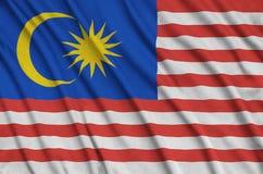 Η σημαία της Μαλαισίας απεικονίζεται σε ένα ύφασμα αθλητικών υφασμάτων με πολλές πτυχές Έμβλημα αθλητικών ομάδων στοκ φωτογραφίες